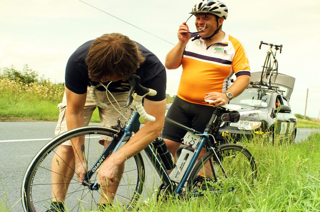 A bike mechanic helps a cyclist get back on the road. Image thanks to Flickr user Stuart-Buchanan used under a Attribution-NoDerivs License